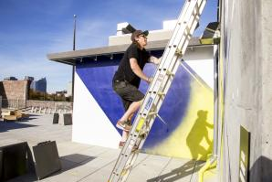 Jake Castro paints a mural on the rooftop of the Warehouse Artists Lofts in 2014. Castro is one of four Sacramento artists commissioned for the Sacramento Mural Festival. He will install his mural at the Crest Theater.
