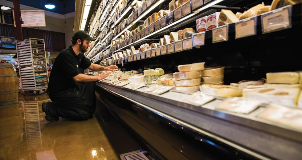 Nugget Market Cheese Manager Kyle Smelosky rearranges product before the afternoon rush