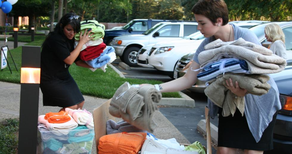Women in Philanthropy members sort through towels donated for local emancipating foster youth.