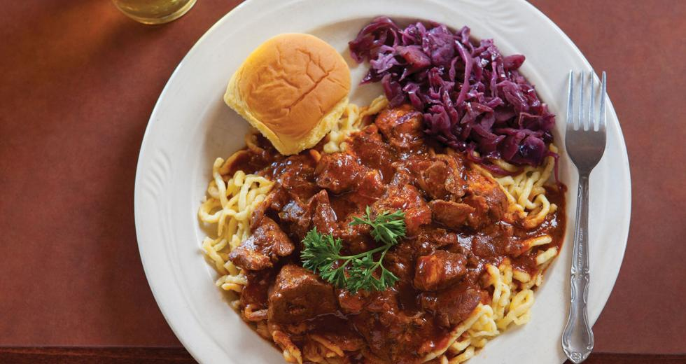 Hungarian pork sirloin goulash stewed with onion, garlic, paprika, caraway and red cabbage, served with spatzle and a pint of Warsteiner Pilsner