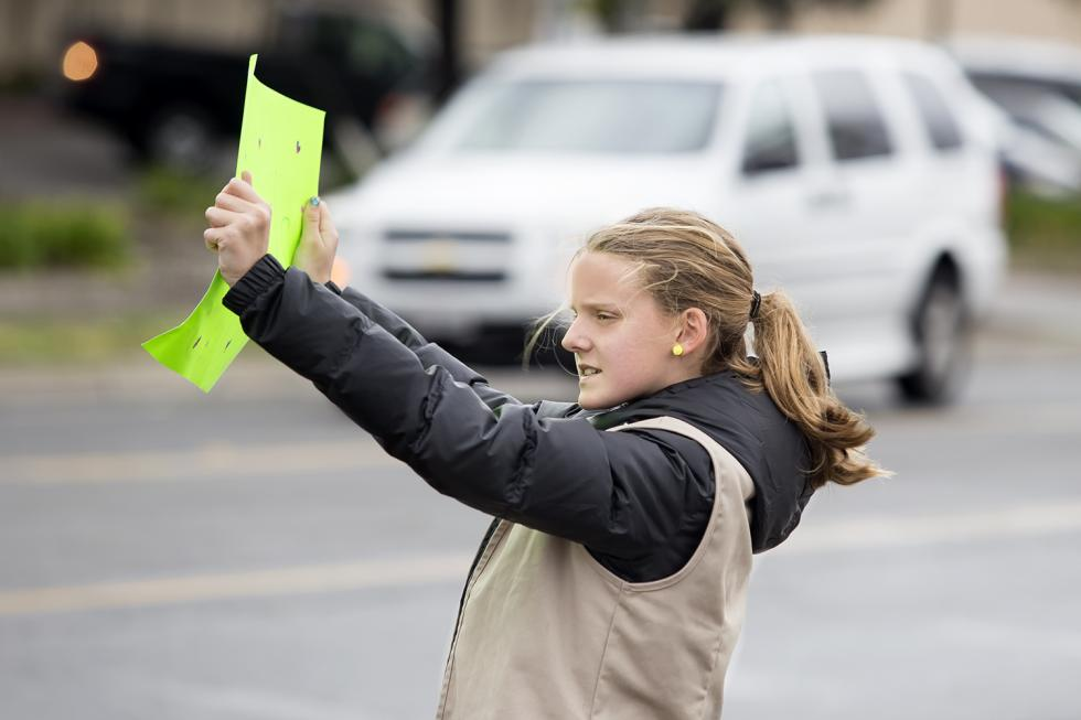 Sophie Esley holds up a sign encouraging drivers to stop for cookies.