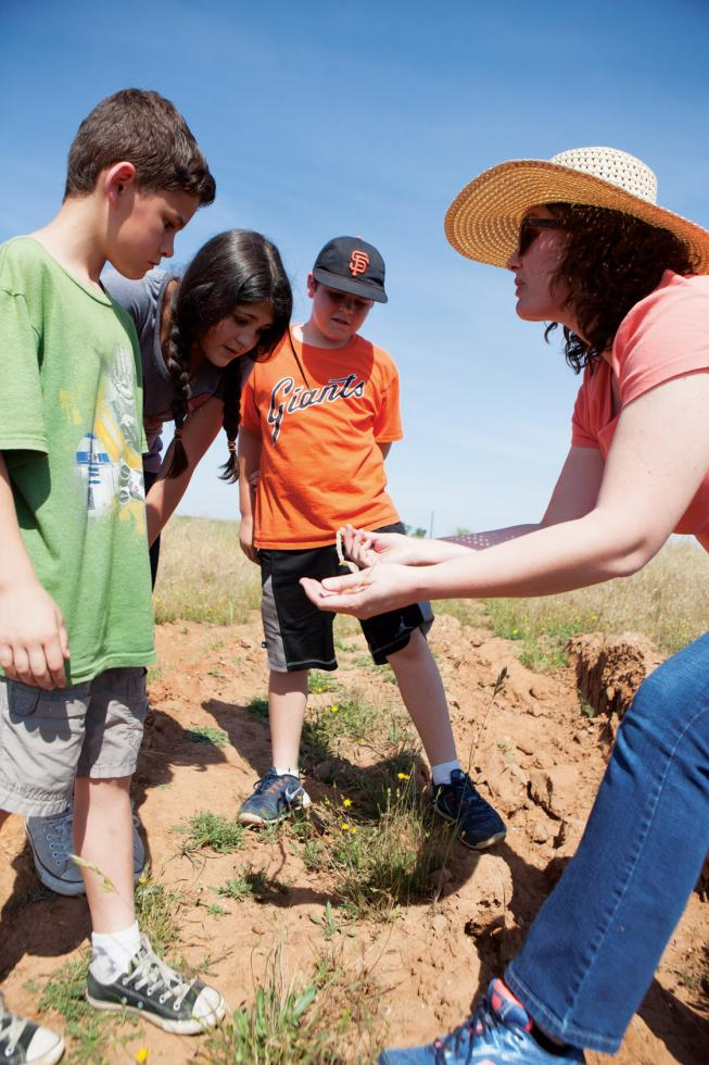 Emily Butler, executive director of Sac Splash, discusses with students the discovery of a snakeskin found inside the vernal pools they were exploring.