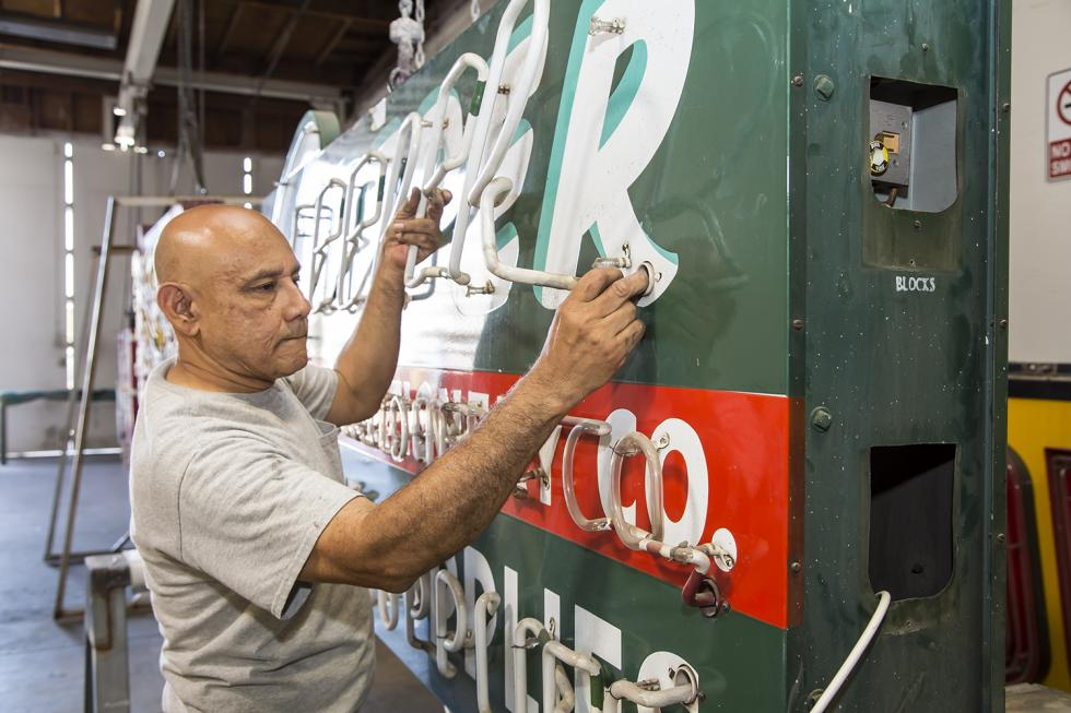 Pacific Neon electrician Sergio Romero removes the neon tubes on the Sleeper Stamps & Stationery sign.