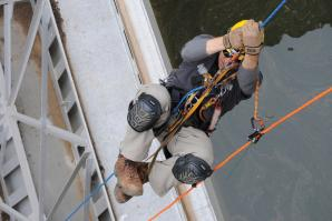 Christopher Abela, a civil engineer with the U.S. Army Corps of Engineers Sacramento District, ascends a climbing rope during an inspection at New Hogan Dam near Valley Springs.