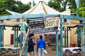 Luke Spates, of NeighborWorks Sacramento, raises the banner for the Oak Park Farmers Market as it opens its seventh season in McClatchy Park.