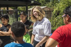 Intern Camryn Agnello leads an ice-breaker game with children attending summer camp at Sacramento Food Bank & Family Services