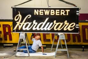 Signs for Newbert Hardware and Tower Records await a tune-up from Pacific Neon electrician Sergio Romero. (Photos by Joan Cusick)