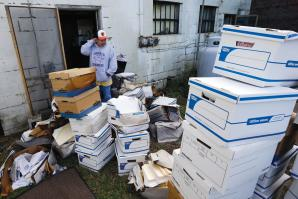 Certified Public Accountant John Sterling looks at damaged boxes of records removed from his Crisfield, Md. office after superstorm Sandy