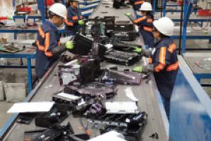 Workers process e-waste at Sims Recycling Solutions in Roseville